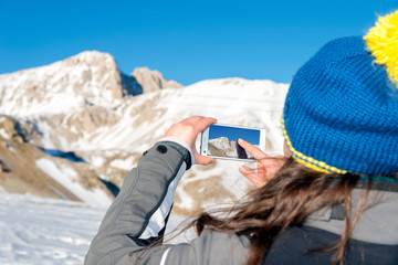 Girl snaps a photo of the mountain, Italy