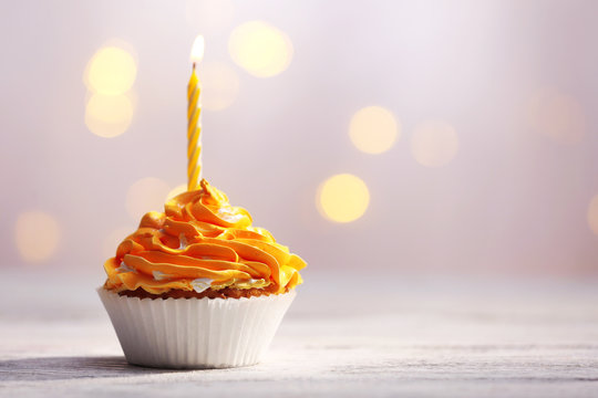 Delicious birthday cupcakes on table on light background