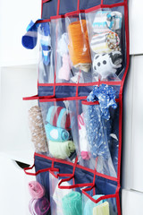 Different socks in hanging bag on closet background