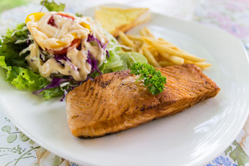grilled salmon steak with french fried and vegetable salad
