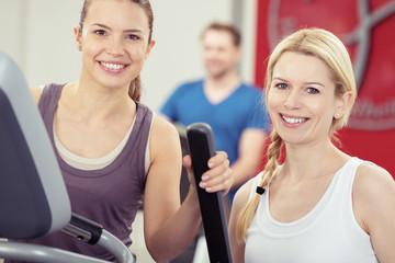 zwei lächelnde frauen trainieren im fitness-center