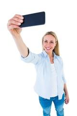 Cheerful blonde taking a selfie with smartphone