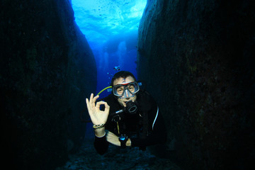 Scuba diver in underwater canyon signals okay