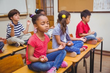 Pupils meditating in lotus position on desk in classroom Wall mural