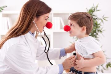 Smiling adorable female doctor clown listen patient heart