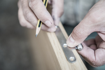 Closeup of carpenter with pencil working on door