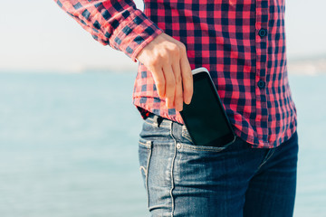 Woman takes out phone of her pocket on beach