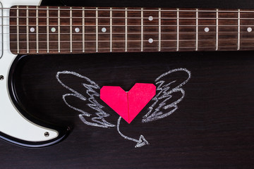 paper heart with wings painted on a musical background