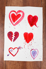 Painted hearts on sheet of paper on wooden table background