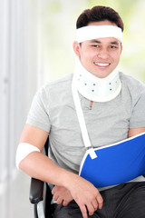 injured young man in wheelchair still look happy