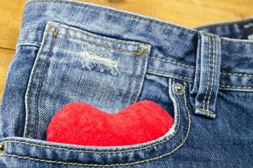 Red heart sticking out of a jeans front pocket
