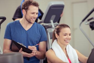 trainer im fitness-studio notiert daten