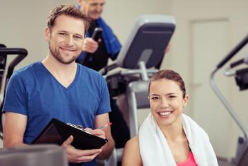 trainer und zufriedene kundin im fitness-studio