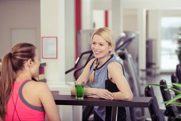 frauen unterhalten sich im fitness-studio an der bar