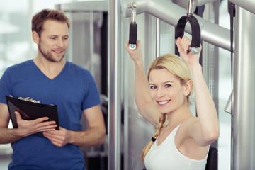 trainer betreut eine frau im fitness-studio