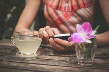 Young woman drinking tea and using her phone