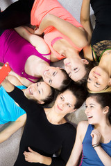 Group of beautiful sporty girls taking selfie, self-portrait wit