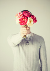 man covering his face with bouquet of flowers