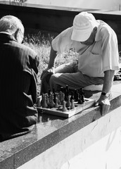 two elderly men playing chess on the street