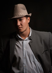 a man in a grey hat on black background