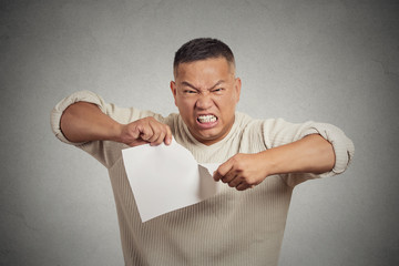 angry man tearing document to pieces grey background