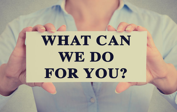 Businesswoman hands holding sign What can we do for you?