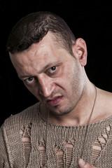 Frowning man portrait looking at camera on black closeup