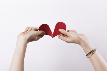 Woman hands tearing paper heart