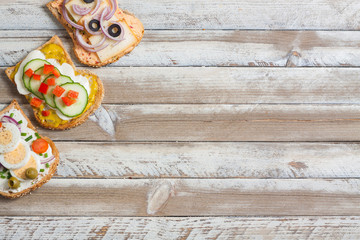 Sandwiches on wooden background, empty space on right