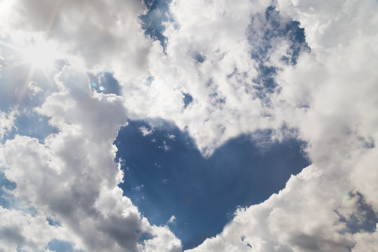 Blue sky with heart shaped form by cloud