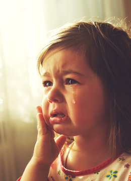 Cute little girl is crying. Toned