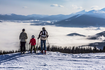 Family of three people stays in front of scenic landscape