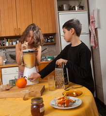 child drinks orange juice from the mixer with a straw
