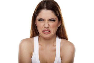 disgusted and frowning young woman on a white background