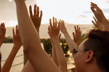 Raising hands to golden sunset sky
