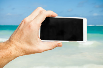 Man using smartphone for taking photo on a beach