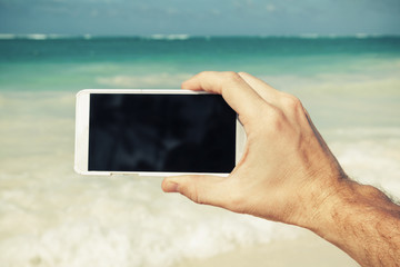 Man using smart phone for taking photo on a beach