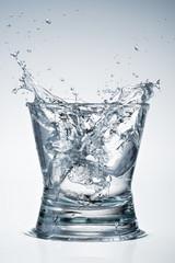 Glass of water. Big splash  with ice.