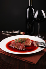 Grilled steak in wine sauce with glass of wine