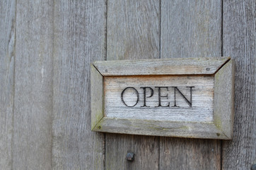 Open sign attached to wood door.
