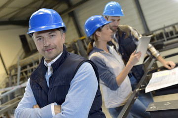 Fototapeta Supervisor in factory with employees in background obraz