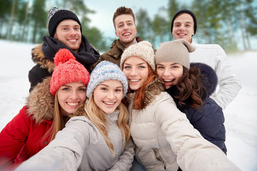 group of smiling friends taking selfie outdoors