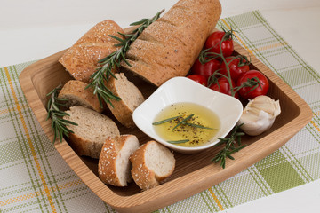 Bread with olive oil ,rosemary on the wooden plate.