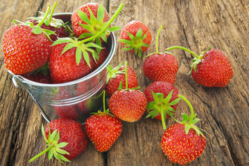 Ripe red strawberries on a wooden background.