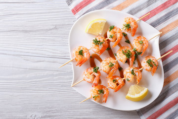 Grilled shrimp on skewers with lemon horizontal top view