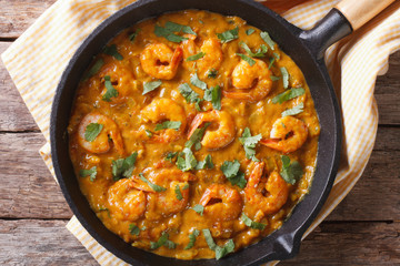 Shrimp in curry sauce in a pan close-up horizontal top view