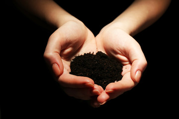 Handful of soil on dark background