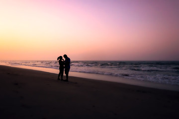 silhouette of couples hugging on the beach