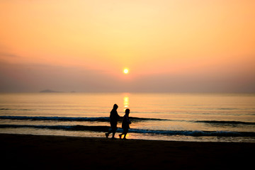 silhouette of couple running on the beach