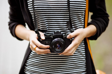 Women's hands holding the vintage film camera